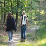 Foto van twee deelnemers die wandelen in het bos