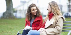 Foto van vrouwen in gesprek op een bankje