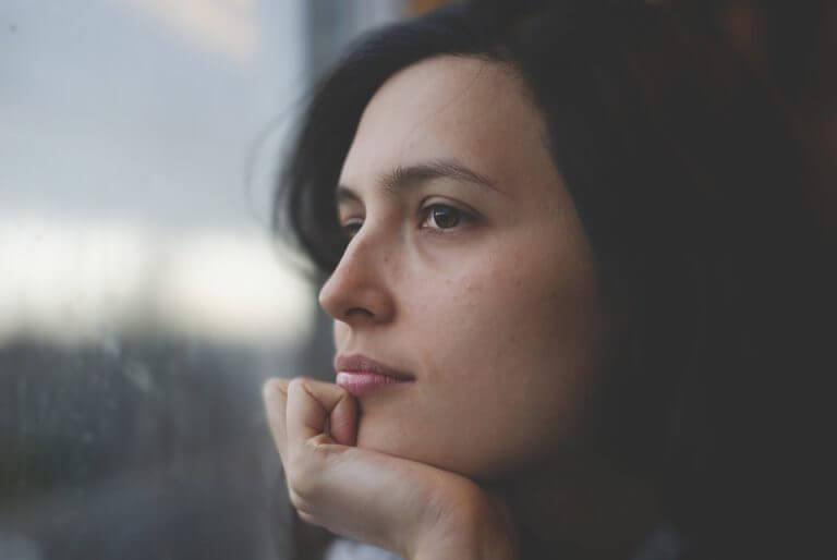 Vrouw kijkt naar buiten en denkt na
