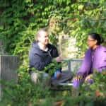 Foto van twee studenten die buiten in de tuin zitten te praten