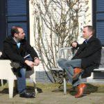 Foto van twee studenten die buiten op het plein zitten te praten