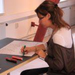 Foto van student die zit te tekenen