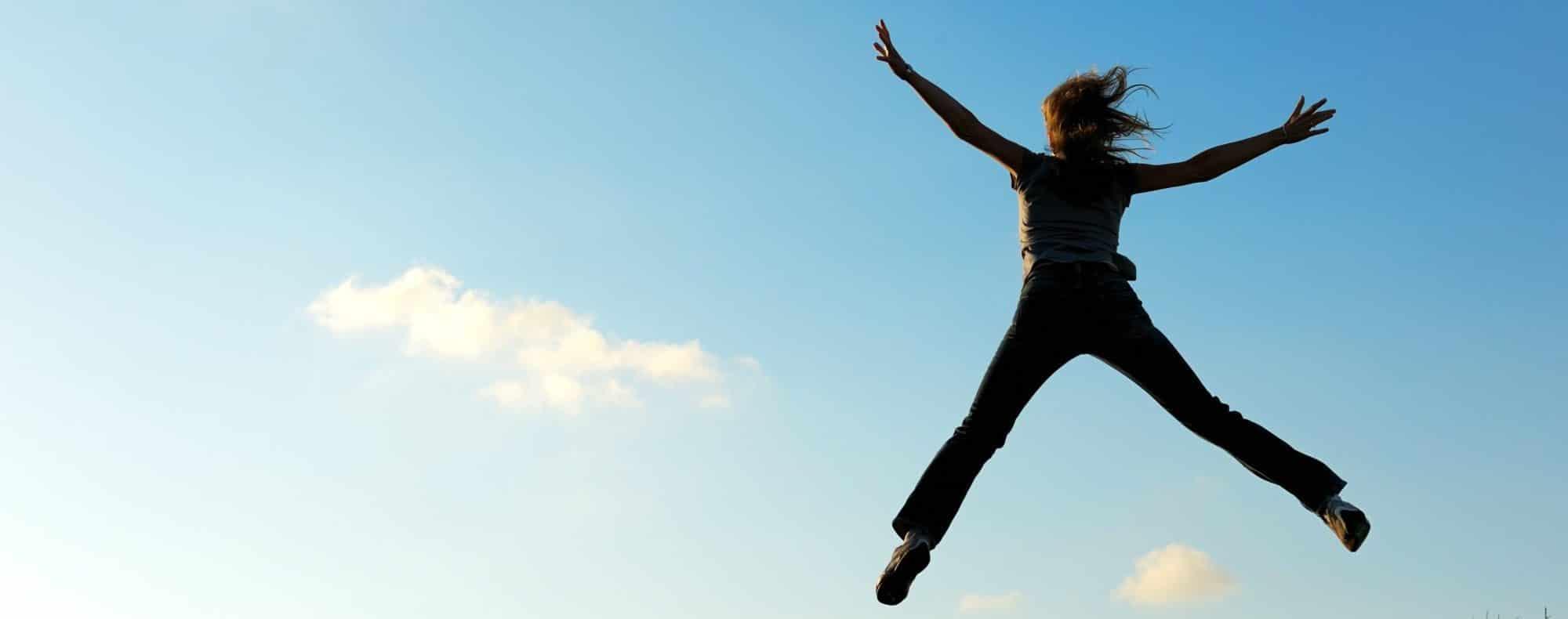 Springende vrouw in de lucht