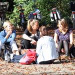 Foto van studenten zittend op de grond in de tuin