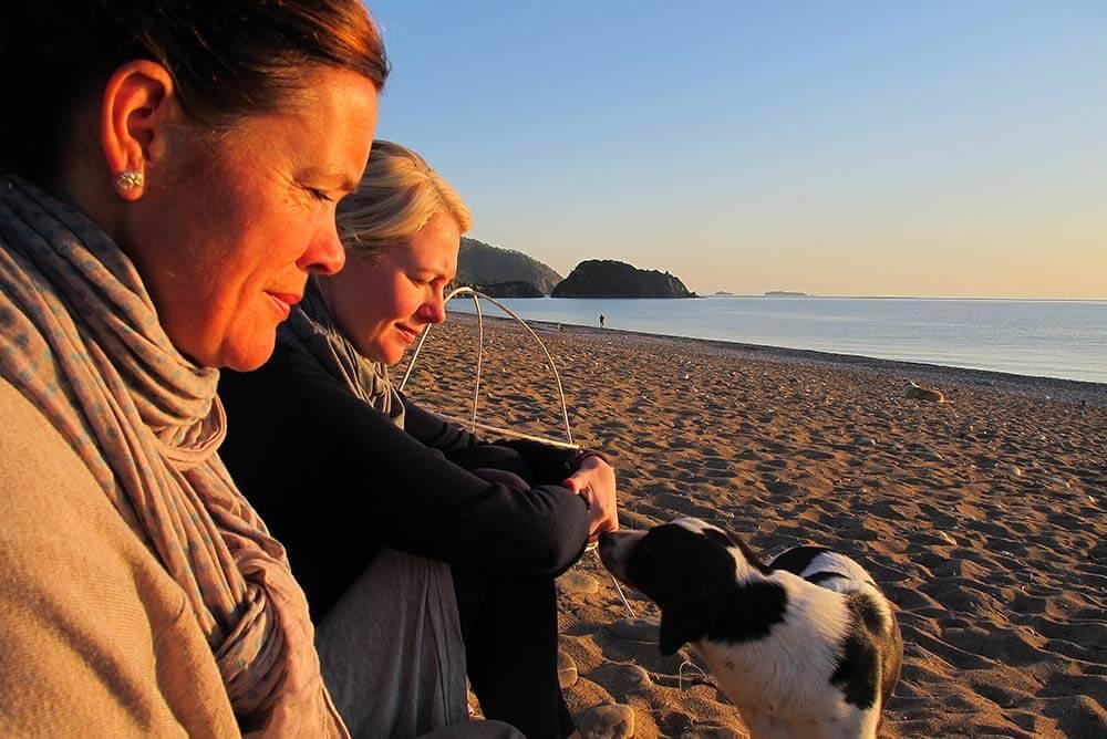 Twee Studenten Met Hond Op Strand